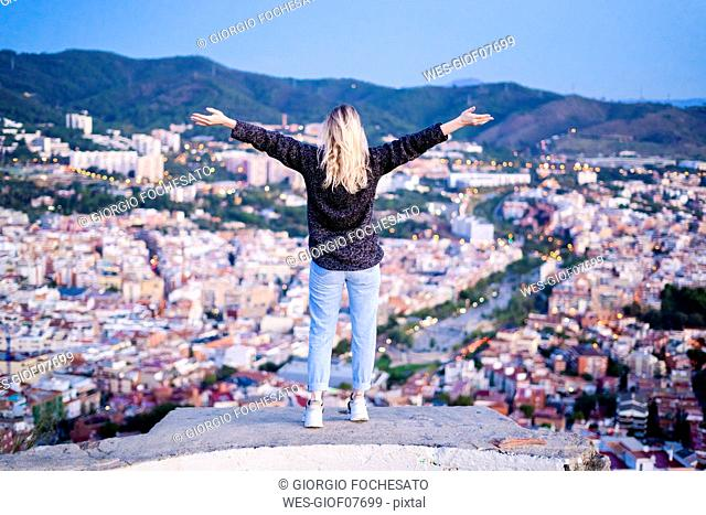 Rear view of carefree young woman standing above the city at sunrise, Barcelona, Spain