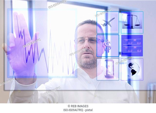 Mature man using interactive computer touchscreen