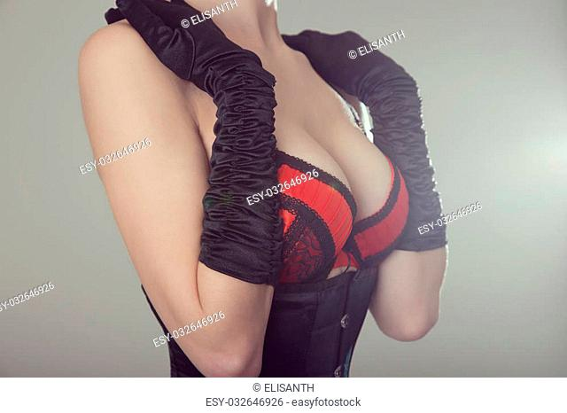 Beautiful woman in black corset and red bra, studio shot with vintage tone