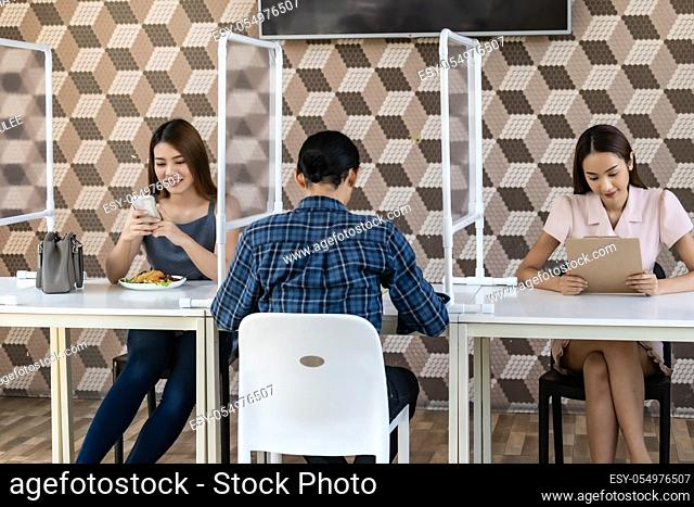 Restaurant customers have a seat with table shield partition for social distancing to reduce infection of coronavirus covid-19 pandemic