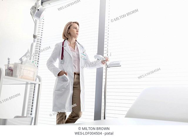 Doctor in medical practice looking out of window