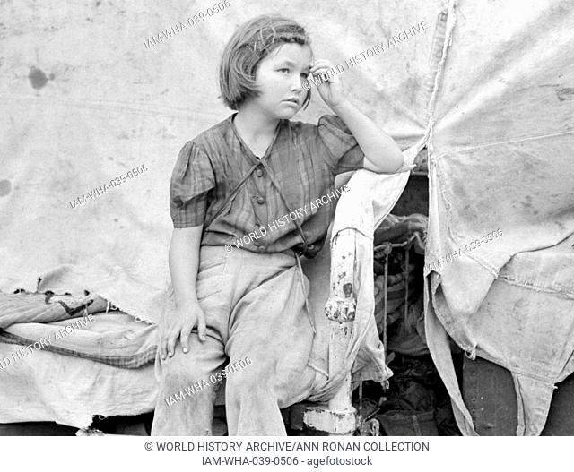 Child of migrant worker sitting on bed in tent home of cotton picking sacks, Harlingen, Texas By Russell Lee, 1903-1986, photographer 19390101