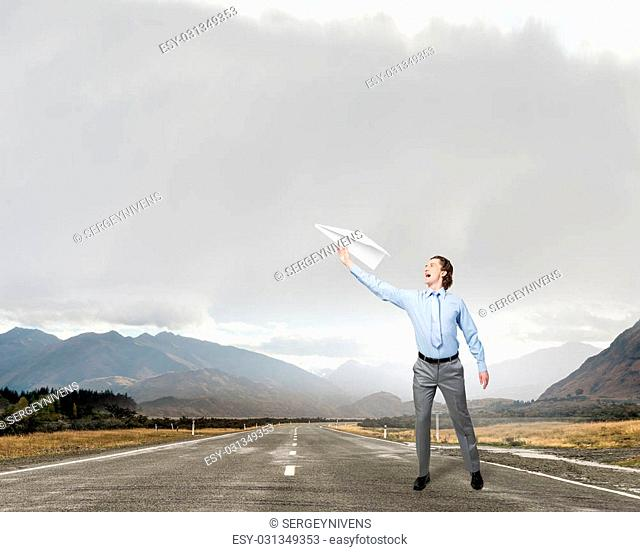 Young businessman on asphalt road with paper plane in hand