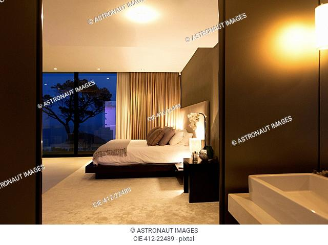 Beige and white bedroom with double bed seen from bathroom at night