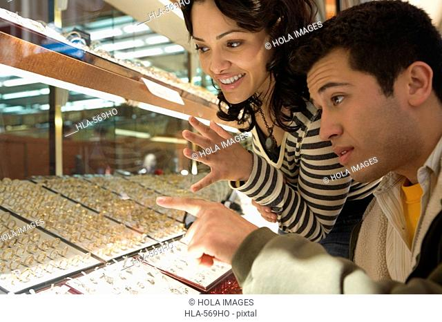 Close-up of a young couple looking at jewelry in a jewelry store