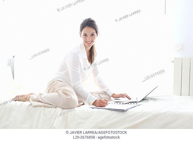 Woman sitting on bed and using  laptop