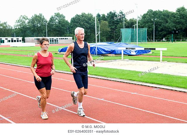 Senior couple running together on a track in a stadium