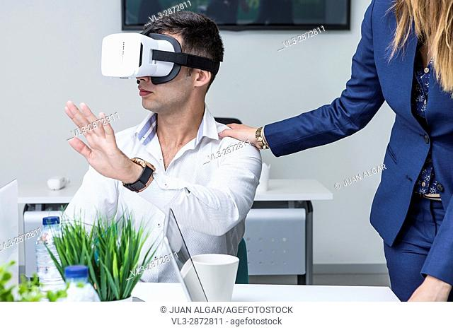 Young man in shirt wearing VR headset and crop woman holding hand on his shoulder