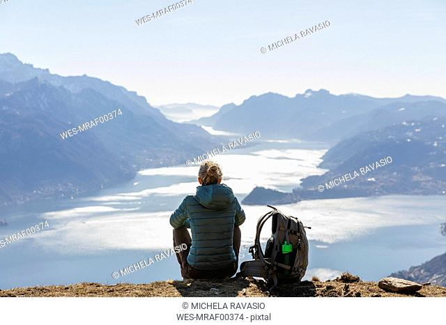 Italy, Como, Lecco, woman on a hiking trip in the mountains above Lake Como sitting down enjoying the view