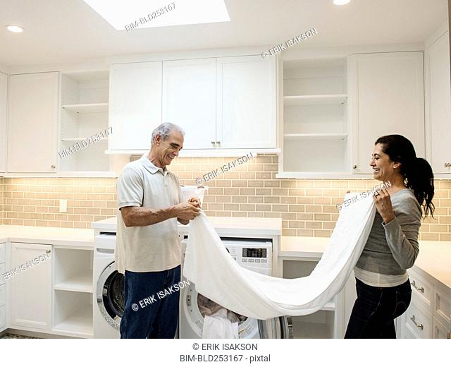 Couple folding towel in modern laundry room