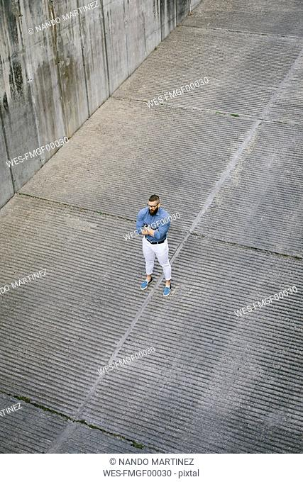 Bearded hipster businessman standing on ramp