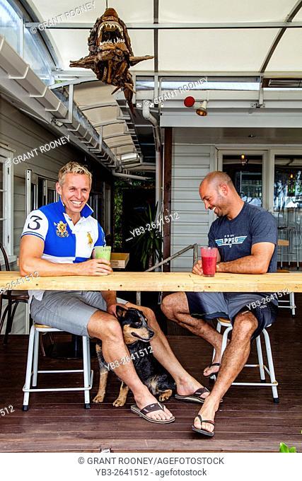 Two Men Sitting At A Beach Side Cafe/Restaurant, Waipu Cove, North Island, New Zealand