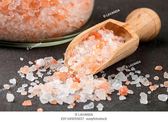 Himalayan pink salt in wooden spoon and jar on a black background. Selective focus
