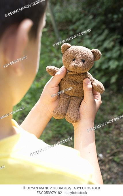 Child hold teddy in a garden