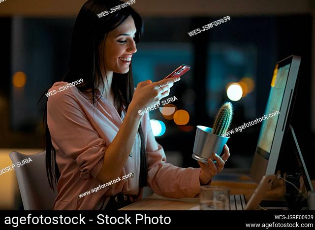 Smiling young woman sitting at desk in office taking photo of cactus