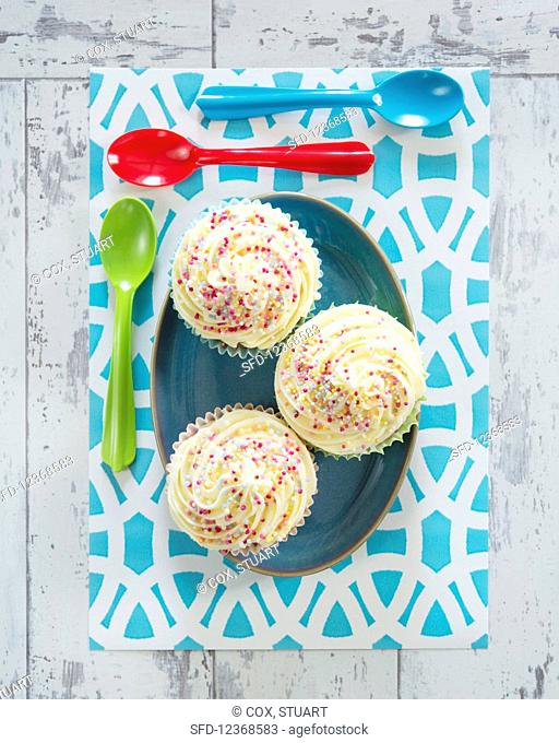 Cupcakes with cream and colorful sugar sprinkles (supervision)
