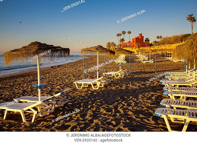 Beach hammocks at sunrise. Bil-Bil castle built in neo-Arab style in 1934, Benalmadena. Malaga province Costa del Sol. Andalusia Southern Spain, Europe
