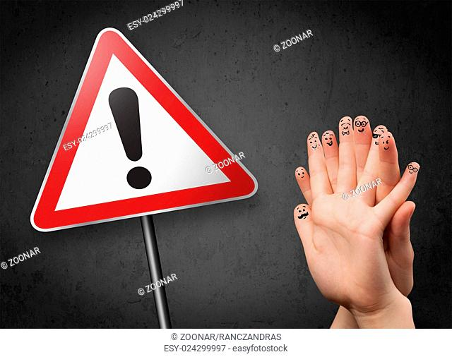 Happy smiley fingers looking at triangle warning sign with exclamation mark