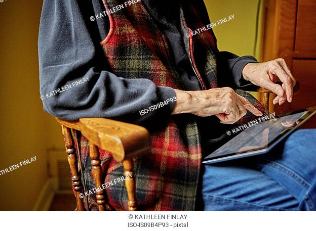Senior woman sitting in chair, using digital tablet, mid section