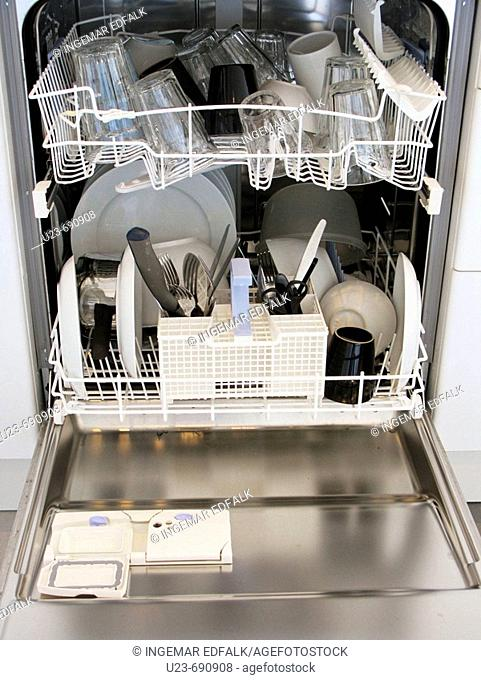 Open washing-up machine, filled with dishes