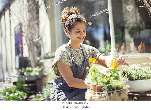 Smiling female florist arranging display at sunny flower shop storefront