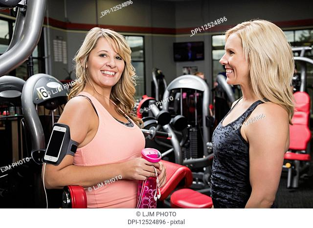 A personal trainer and her client pausing and talking after working out at a fitness facility; Spruce Grove, Alberta, Canada