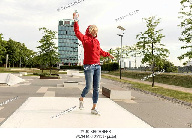 Carefree senior woman wearing red hoodie outdoors
