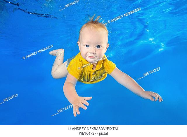 little boy in a yellow shirt learns to swim underwater in the pool