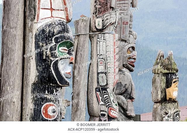 Weathered totem poles stand facing the sea at the Namgis burial ground on Cormorant Island. Alert Bay, British Columbia, Canada