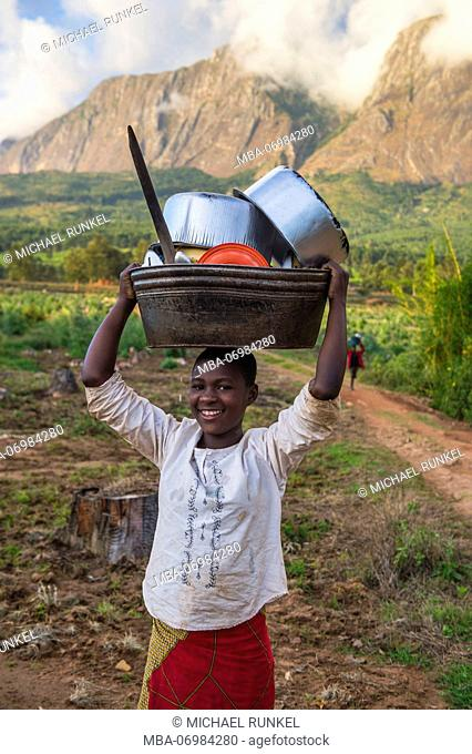 Girl with washed dishes on her her before Mount Mulanje, Malawi, Africa