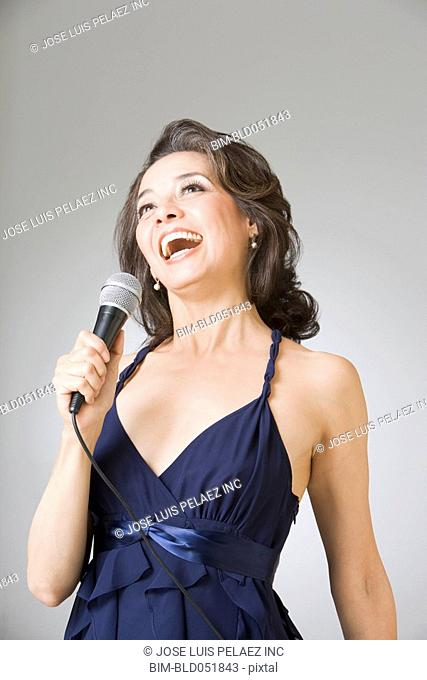 Hispanic woman singing into microphone