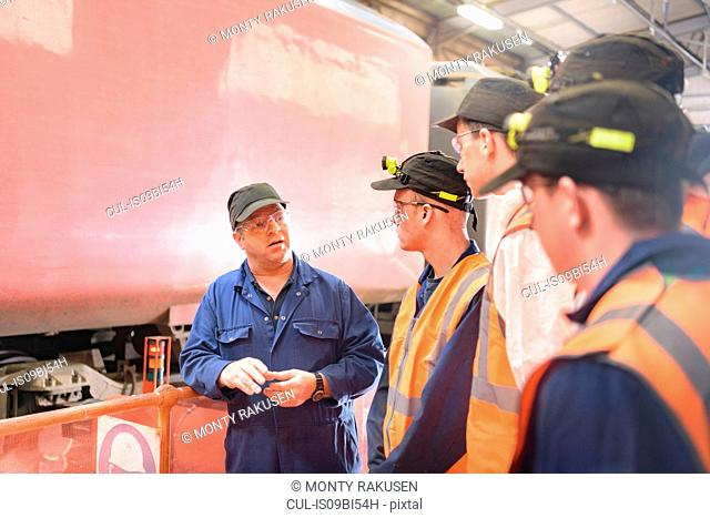 Engineer instructing apprentices with locomotive wheel lathe in train engineering factory