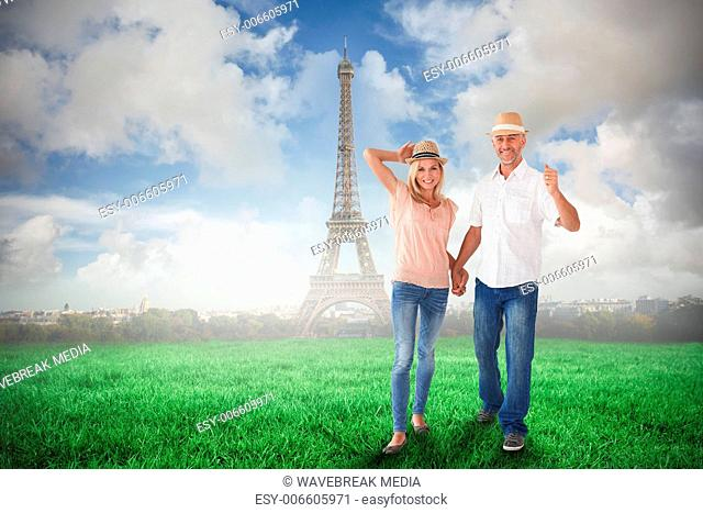 Composite image of happy couple walking holding hands