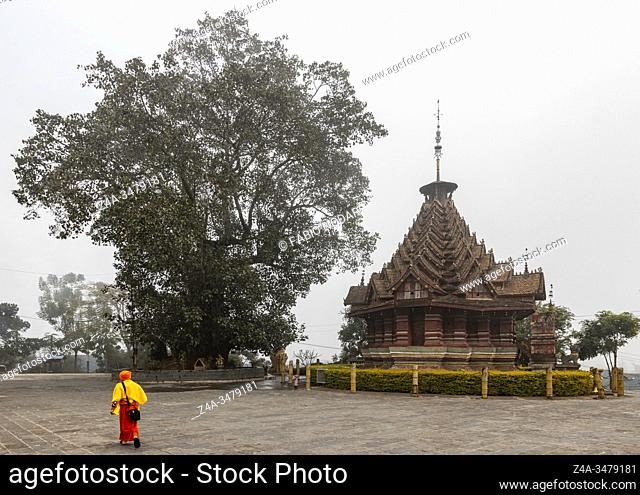 Jinghong, China - December 31, 2019: Octagonal Pavilion Jingzhen Bajiao Ting in Xishuangbanna and monk on foreground
