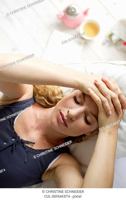 Woman lying on sofa with hands on head