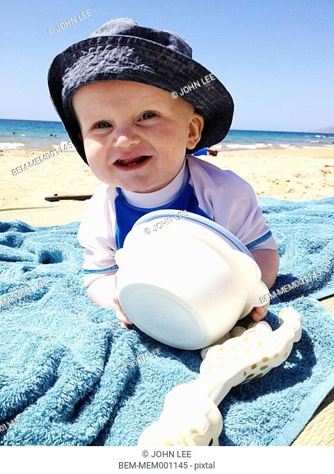 Caucasian baby playing on towel on beach