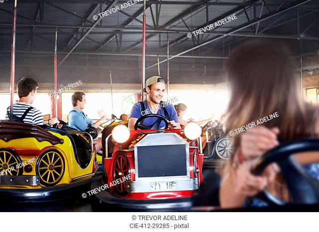 Young man riding bumper cars at amusement park