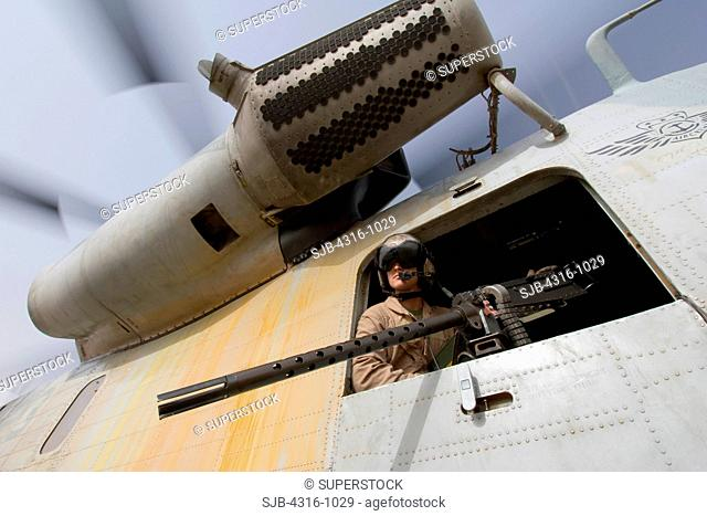 A US Marine Door Gunner Peers from a CH-53D Sea Stallion Helicopter from Above an M2 .50 Caliber Machine Gun