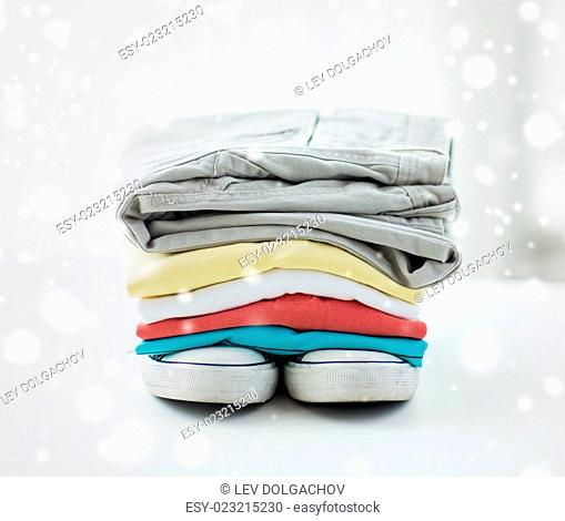 clothes, personal staff and objects concept - close up of folded shirts, pants and shoes on table at home over snow effect