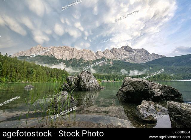 Rocks on the shore, Lake Eibsee lake in front of Zugspitze massif with Zugspitze, dramatic Mammaten clouds, Wetterstein range, near Grainau, Upper Bavaria