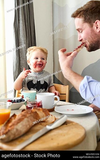 Portrait of smeared little boy at breakfast table watching his father eating bread with jam