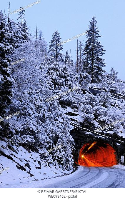 Red Wawona Road tunnel and blue snow covered mountain at dawn in Yosemite National Park
