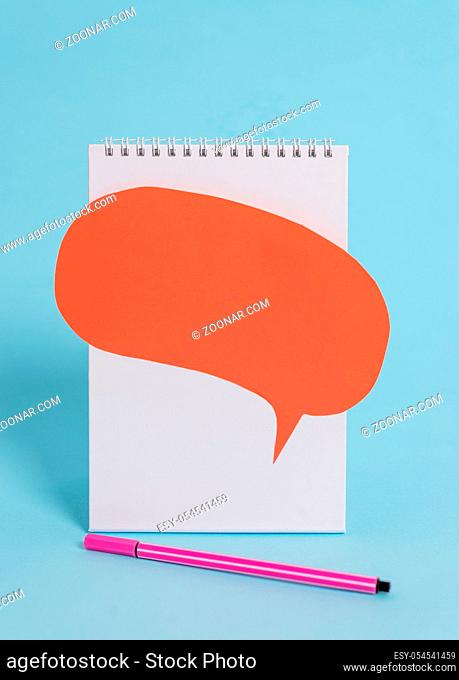 Standing blank spiral notepad speech bubble pen lying cool background