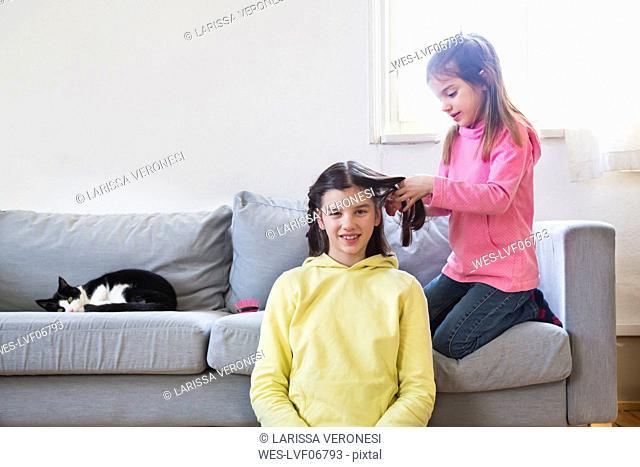 Little girl braiding her sisterƒ.s hair