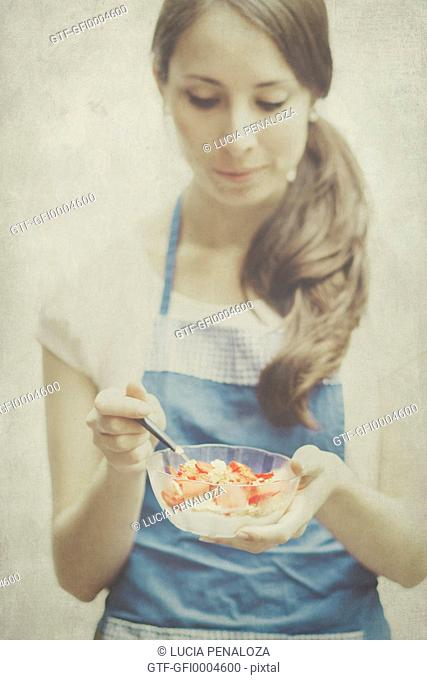 Young woman holding a bowl with strawberries