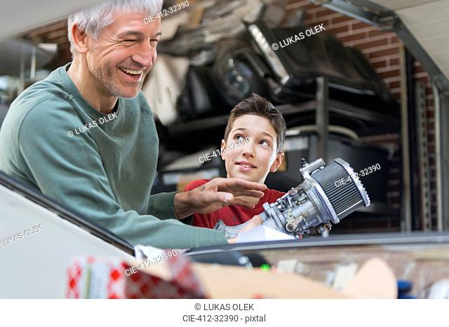 Smiling father and son fixing car engine in auto repair shop