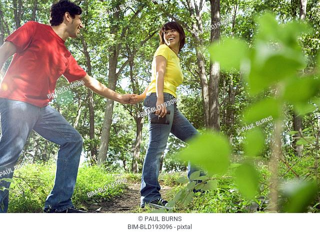 Couple holding hands in forest