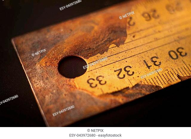 Old rusty metal ruler with numbered label cracking on black background surface with free copy space