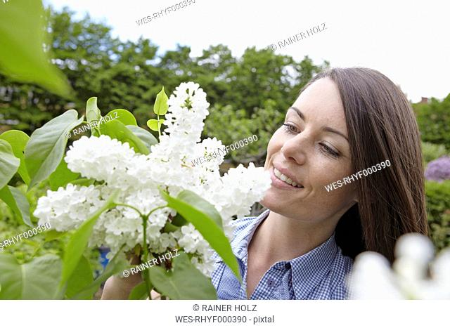 Germany, Cologne, Young woman holding tree blossom, smiling