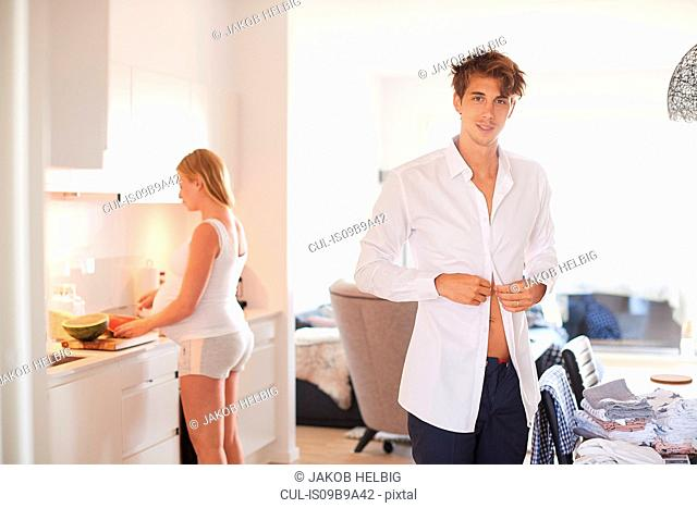 Portrait of man buttoning shirt and pregnant girlfriend in kitchen